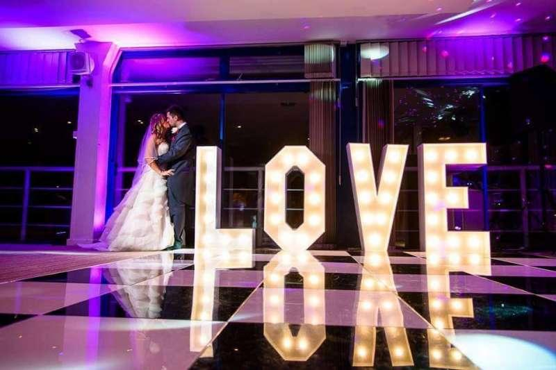 wedding couple standing next to love letters
